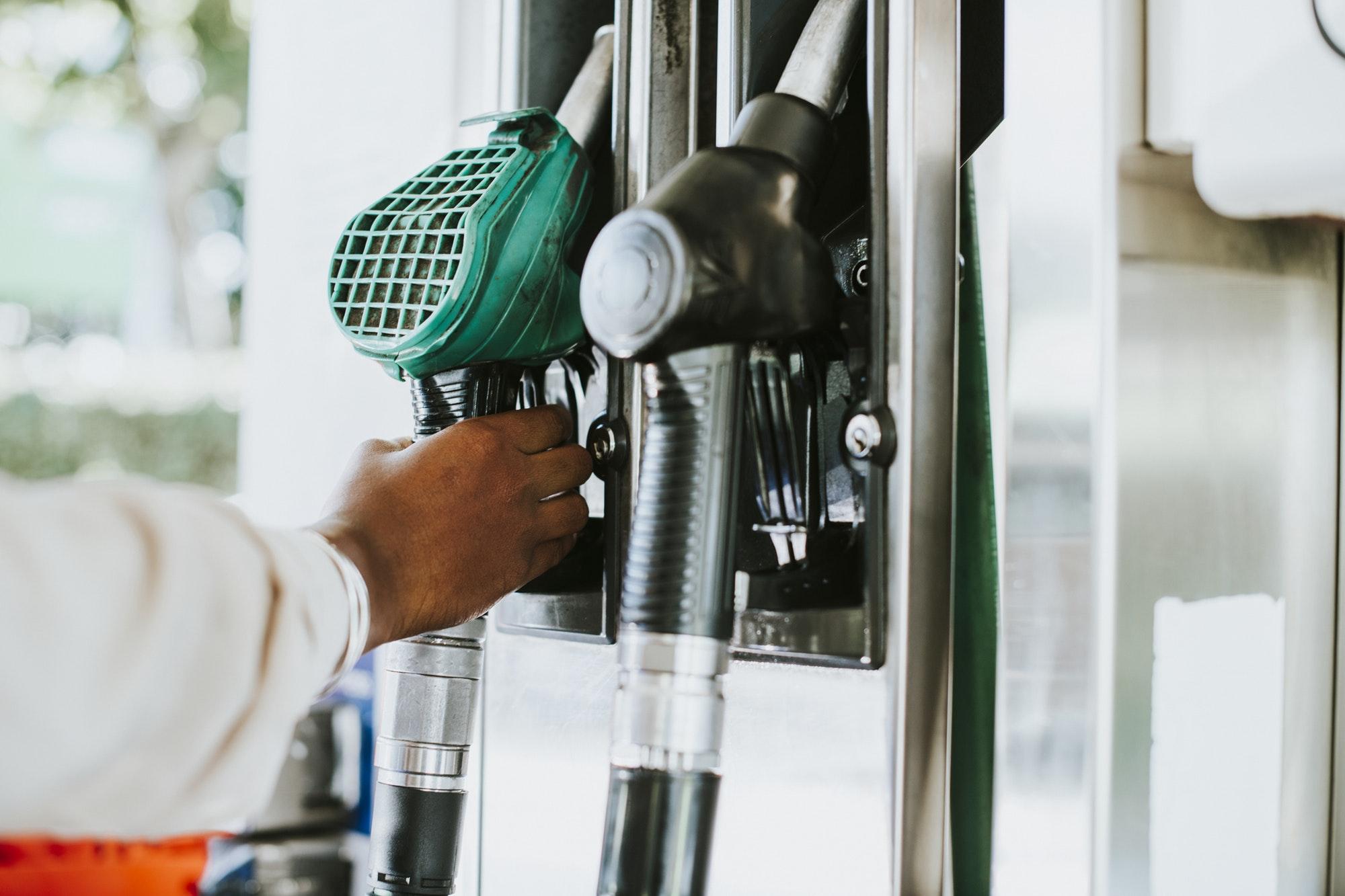 Man grabbing a fuel nozzle to refuel his vehicle