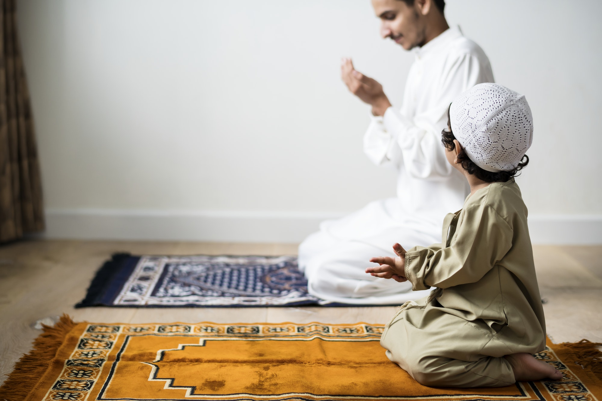 Muslim boy learning how to make Dua to Allah